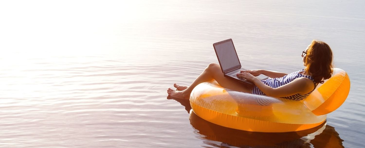 Woman on a pool float in a lake working on a laptop.