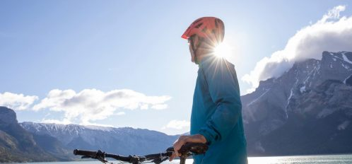 Man standing next to bike with lake and mountains in the background.