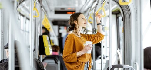Woman standing on a shuttle bus with a coffee.